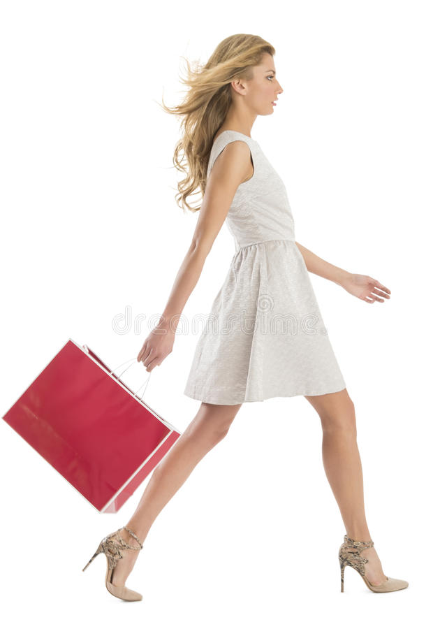 Vista laterale della donna che cammina con il sacchetto della spesa fotografia stock libera da diritti