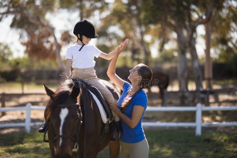 Vista laterale della donna che dà livello cinque alla ragazza che si siede sul cavallo immagine stock libera da diritti