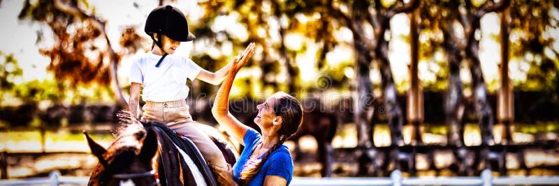 Vista laterale della donna che dà livello cinque alla ragazza che si siede sul cavallo fotografie stock