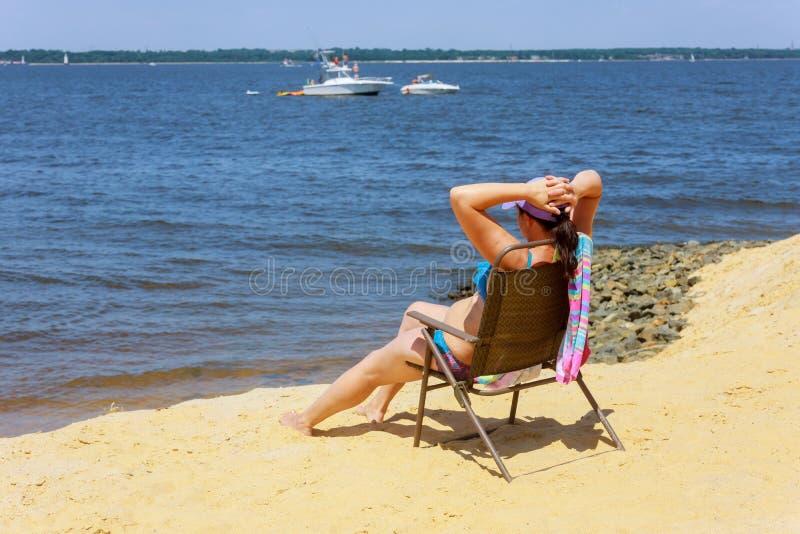 Vista laterale della donna che si siede sulla sedia la spiaggia La giovane donna in bikini sta rilassandosi sulla spiaggia immagine stock