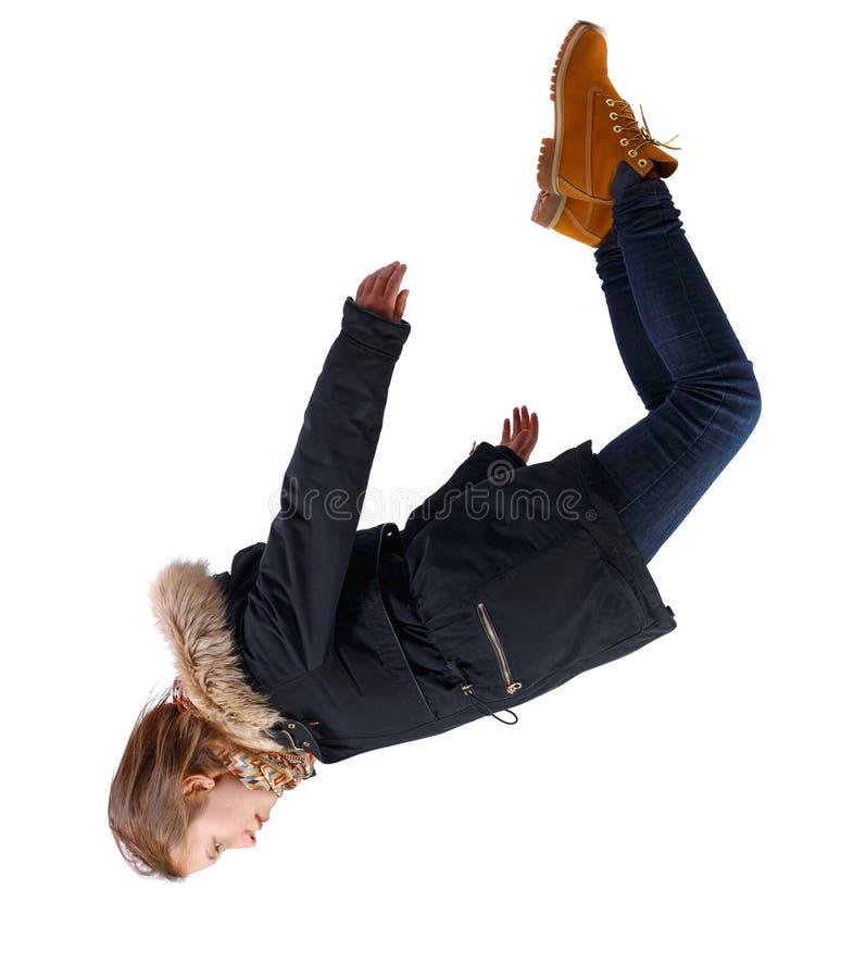 Vista laterale della donna con giacca invernale a gravità zero o caduta fotografia stock libera da diritti