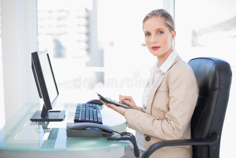Vista laterale della donna di affari bionda che per mezzo del calcolatore immagini stock