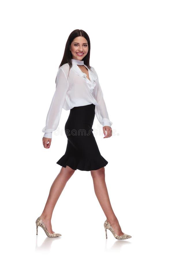 Vista laterale della donna di affari sexy a fare un passo nero della gonna fotografia stock
