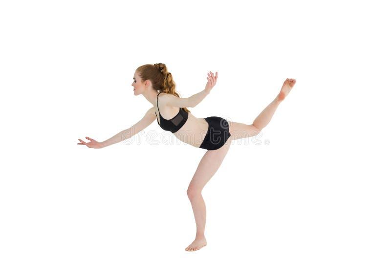 Vista laterale della donna sportiva che sta su una gamba fotografia stock
