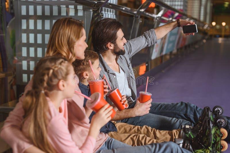 vista laterale della famiglia con le bevande che prendono selfie mentre riposando dopo avere pattinato immagine stock