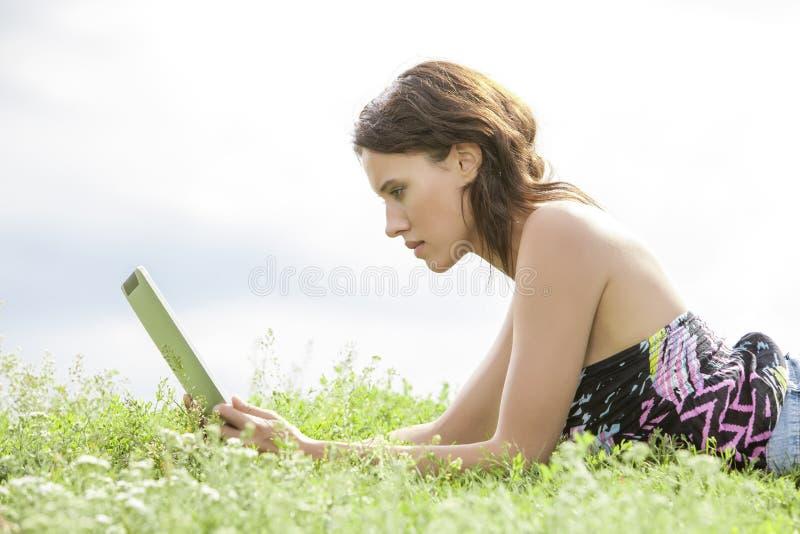 Vista laterale della giovane donna che per mezzo del PC della compressa mentre trovandosi sull'erba contro il cielo fotografia stock