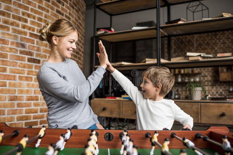 vista laterale della madre felice e del figlio che danno l'un l'altro livello cinque mentre giocando calcio-balilla insieme immagine stock libera da diritti