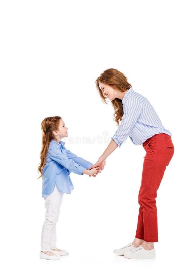 vista laterale della madre felice e della figlia della testarossa che si tengono per mano e che si sorridono immagine stock libera da diritti