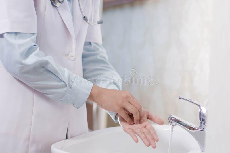 Vista laterale della mano femminile di medico che lava la sua palma nel lavandino bianco con il flusso continuo dell'acqua facend immagini stock