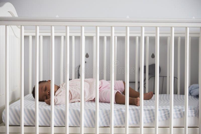 Vista laterale della neonata che dorme in culla della scuola materna immagine stock