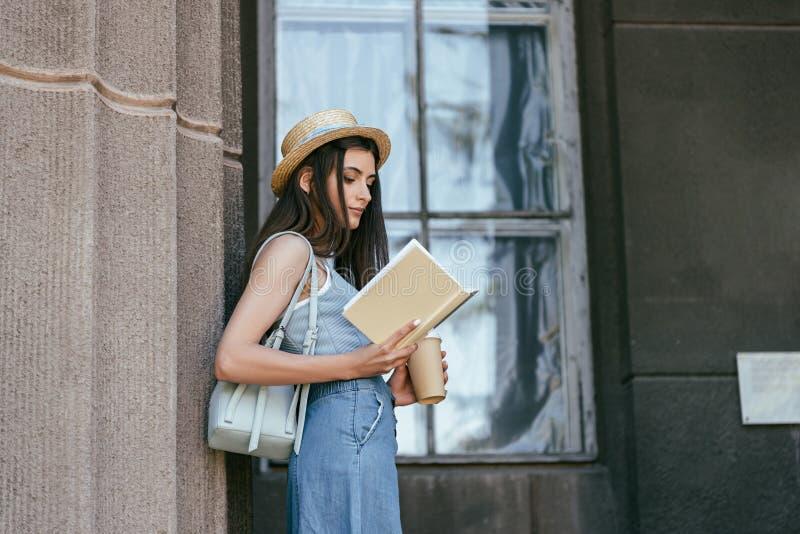 vista laterale della ragazza attraente in cappello che tiene caffè per andare ed il libro di lettura fotografia stock