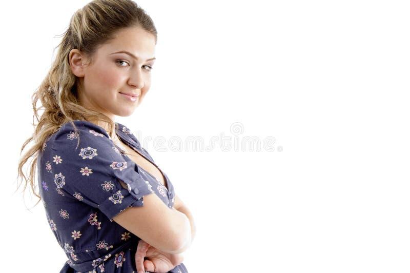 Vista laterale della ragazza sorridente con le braccia attraversate fotografia stock