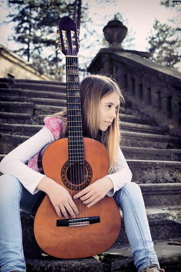 Vista laterale della ragazza vaga con la chitarra che si siede sulle scale fotografia stock libera da diritti