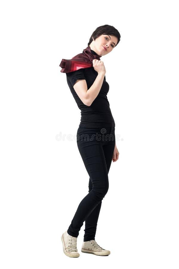 Vista laterale della sciarpa affascinante della tenuta della donna di moda che esamina macchina fotografica immagine stock
