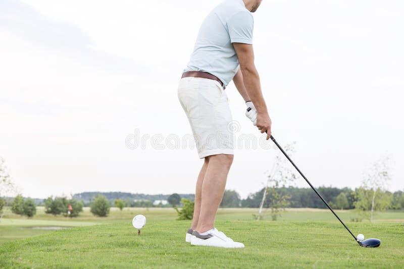 Vista laterale della sezione bassa dell'uomo che gioca golf contro il chiaro cielo immagini stock