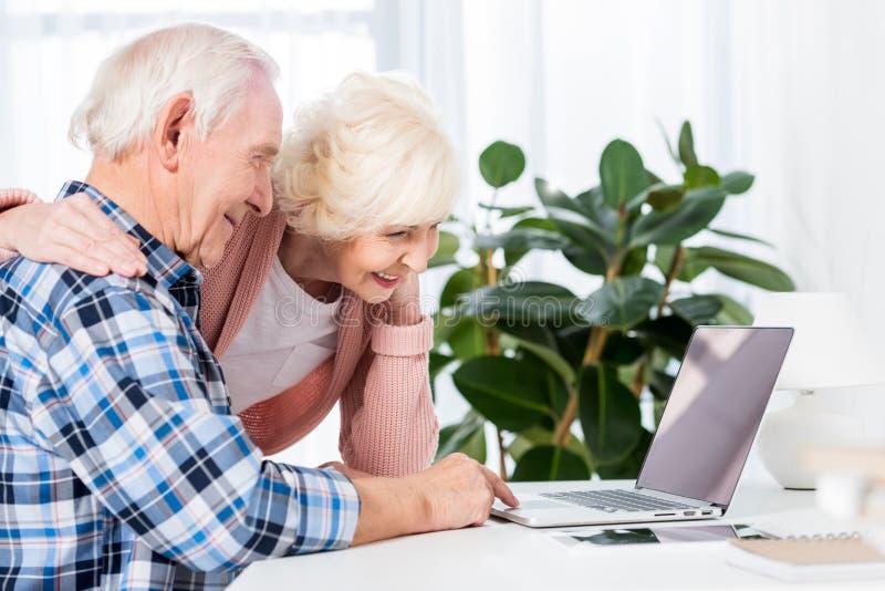 vista laterale delle coppie senior sorridenti facendo uso del computer portatile insieme fotografia stock libera da diritti