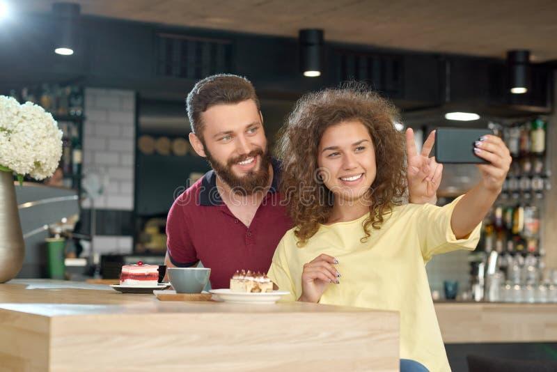 Vista laterale delle coppie sorridenti che prendono selfie mentre data in caffè fotografie stock libere da diritti