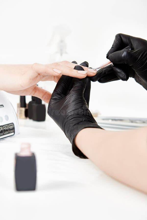 Vista laterale delle mani del manicure in guanti che applicano la lucidatura del gel fotografie stock libere da diritti