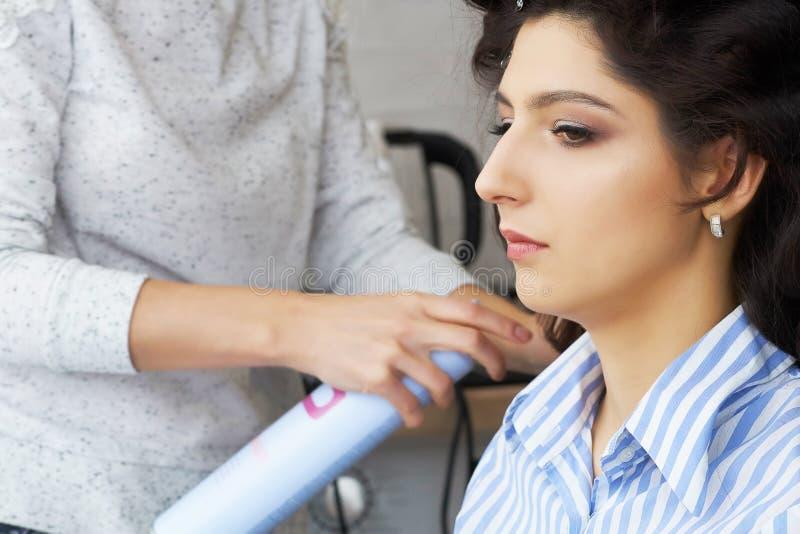 Vista laterale delle mani del ` s del parrucchiere facendo uso della lacca sui capelli del ` s del cliente al salone immagini stock