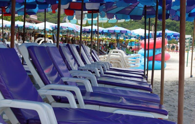 Vista laterale delle sedie e dell'ombrello sulla spiaggia immagini stock