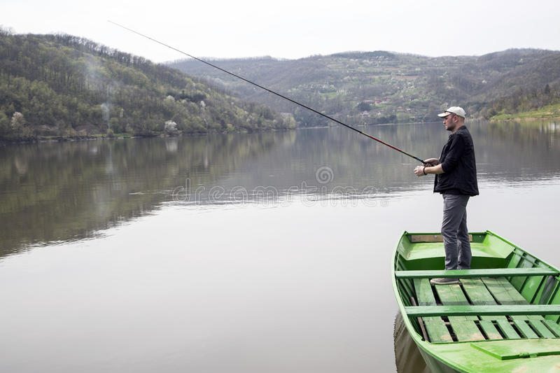 Vista laterale dello sport Fisher Fishing From Green Canoe che gode della sua vacanza sul bello lago fotografie stock