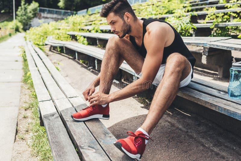 vista laterale dello sportivo che lega i laccetti mentre sedendosi sul banco allo sport immagini stock libere da diritti