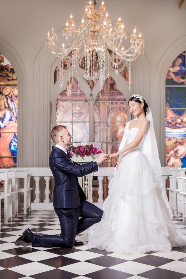 Vista laterale dello sposo che mette anello sul dito della sposa felice nella chiesa fotografia stock