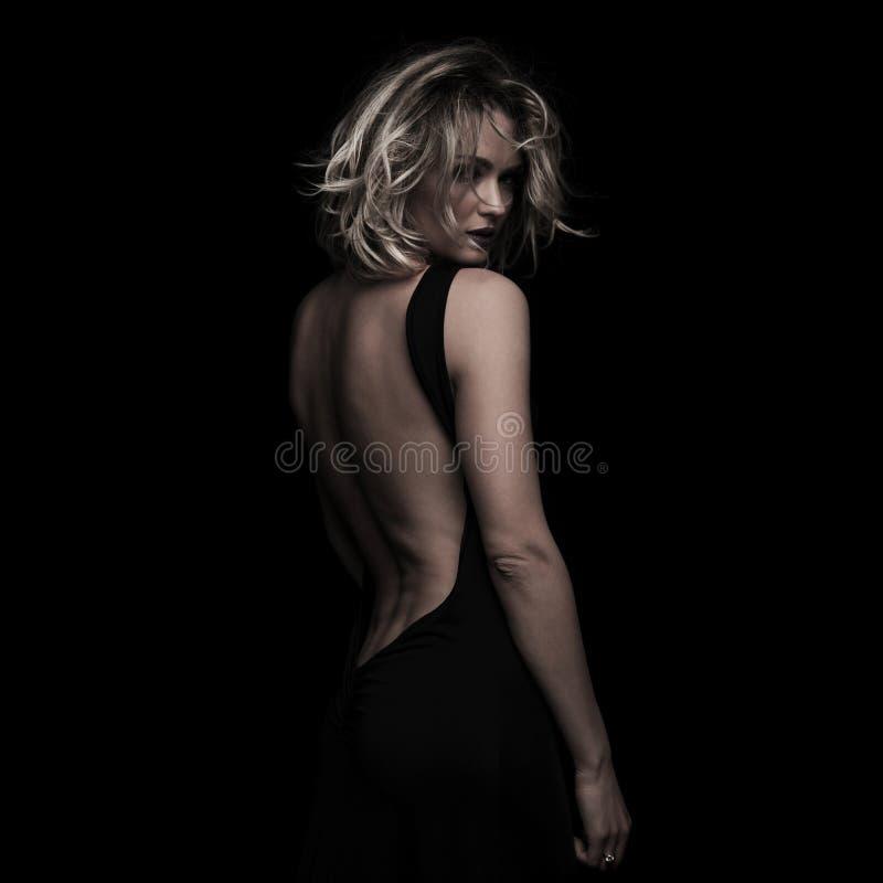 Vista laterale di bella donna bionda che porta vestito con ampia scollatura sulla schiena nero immagine stock