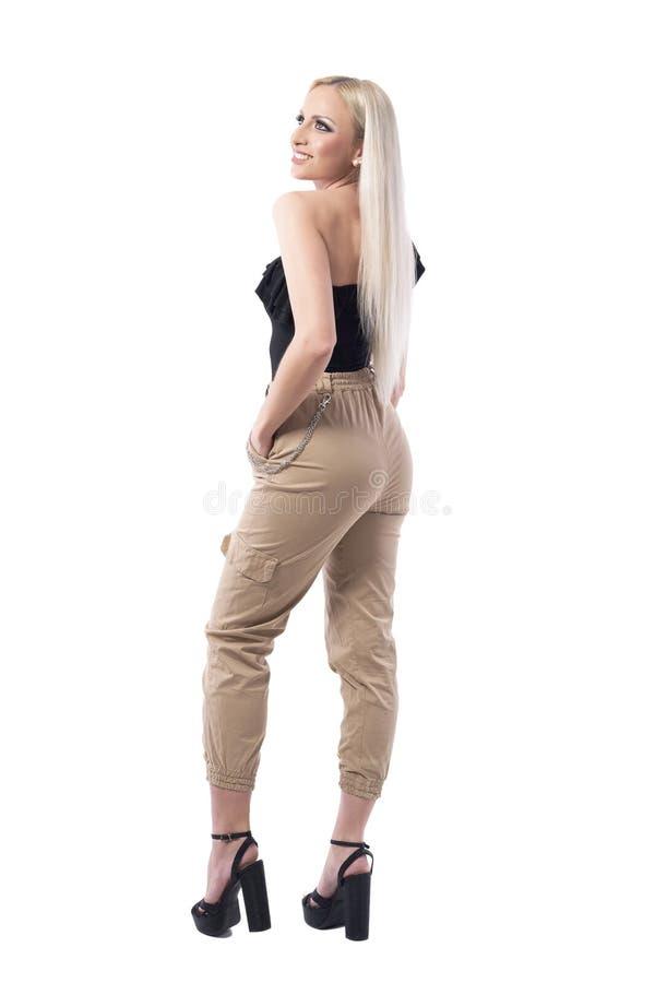 Vista laterale di bella giovane donna alla moda bionda fuori nel cercare sorridente superiore della spalla fotografie stock libere da diritti
