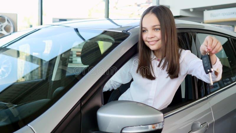 Vista laterale di bella neonata che distoglie lo sguardo e che sorride mentre sedendosi in una nuova automobile in un salone dell fotografie stock