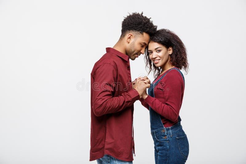 Vista laterale di belle giovani coppie afroamericane in camice classiche che si tengono per mano, esaminandosi reciprocamente e s immagini stock libere da diritti