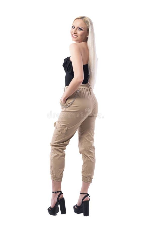 Vista laterale di bellezza bionda della giovane donna nel sembrare elegante di stile della via che sorride alla macchina fotograf fotografie stock libere da diritti