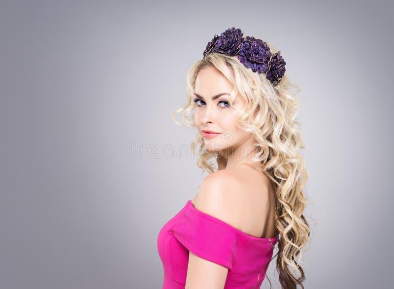 Vista laterale di bello biondo indossando una fascia porpora del fiore fotografie stock