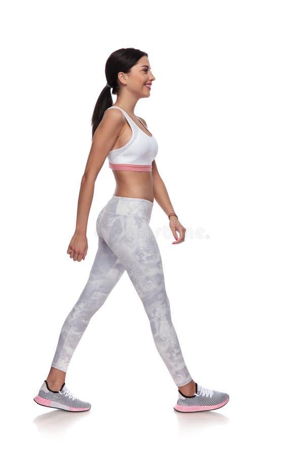 Vista laterale di camminata sorridente della donna di forma fisica immagine stock libera da diritti