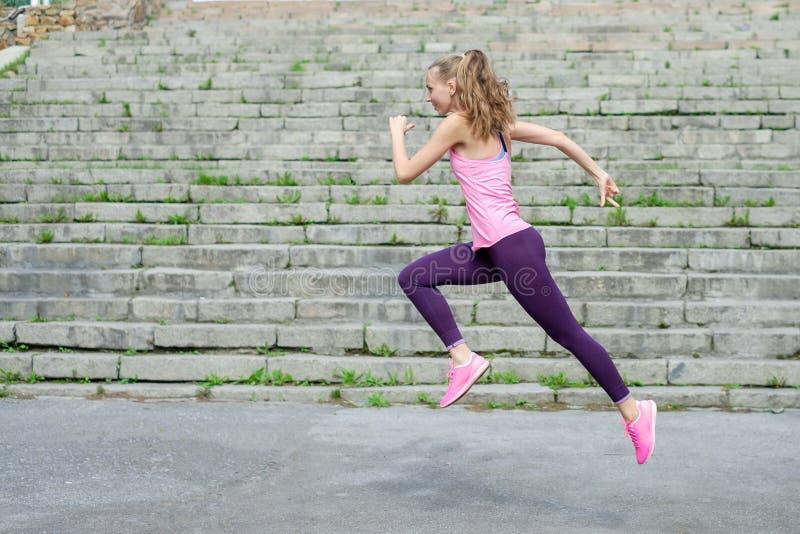 Vista laterale di giovane atleta corrente sportivo attivo del corridore della donna con il peso di perdita di forma fisica di sal immagini stock