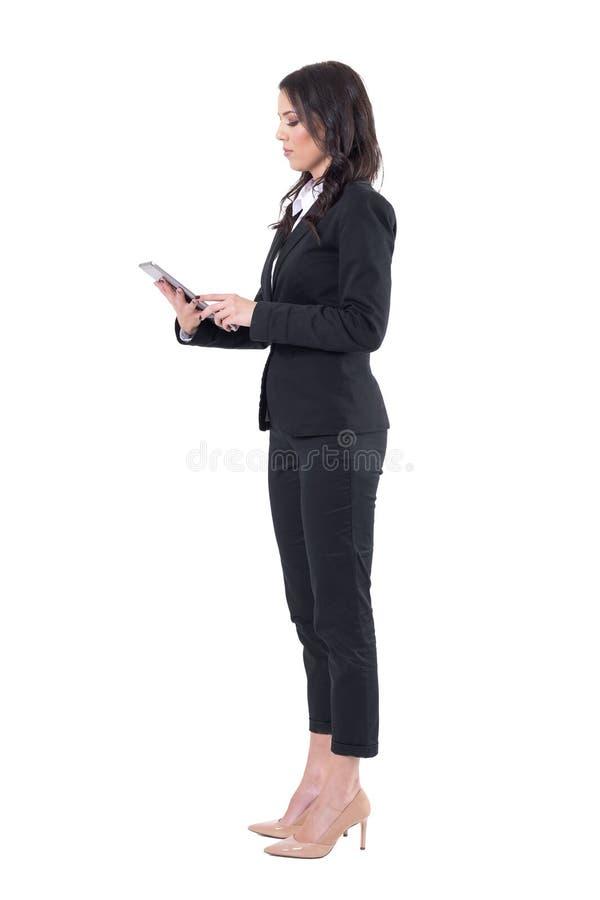 Vista laterale di giovane donna elegante di affari in vestito facendo uso del computer della compressa fotografia stock