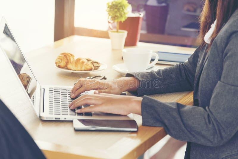 Vista laterale di giovane donna lavoratrice che per mezzo del computer portatile Concetto di affari di comunicazione immagine stock libera da diritti