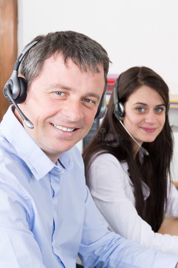 vista laterale di giovane gruppo attraente di donna e dell'uomo in una call center fotografie stock libere da diritti