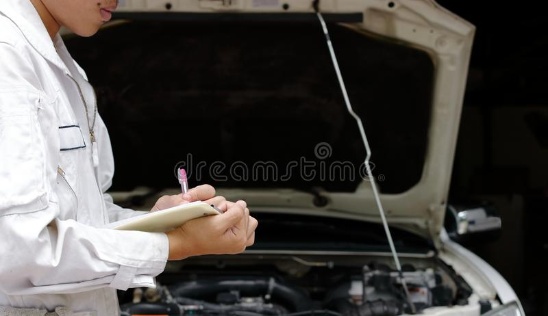 Vista laterale di giovane meccanico professionista nella scrittura uniforme sulla lavagna per appunti contro l'automobile in capp immagini stock libere da diritti