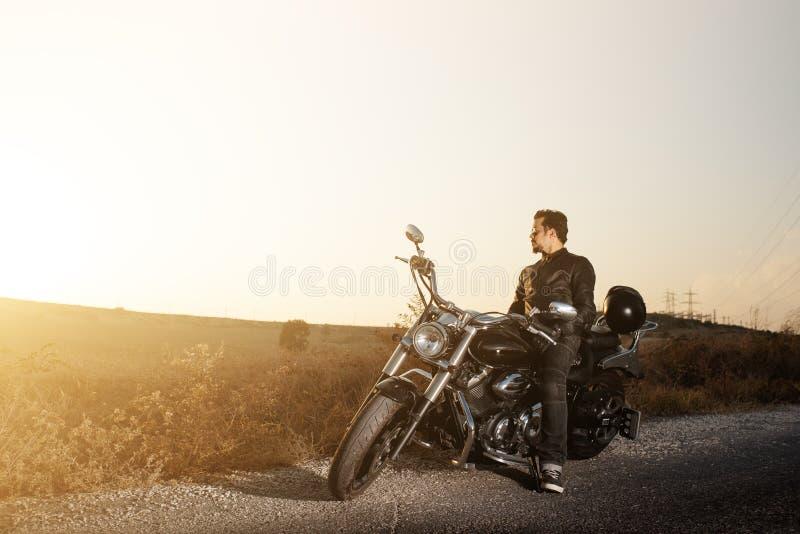 Vista laterale di giovane motociclista maschio che si siede dal lato della strada contro il tramonto mentre viaggiando in bici immagine stock libera da diritti