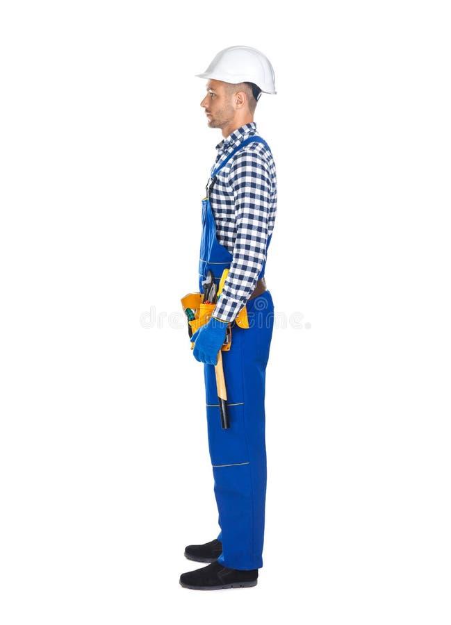 Vista laterale di giovane muratore in cinghia dello strumento e dell'uniforme immagini stock libere da diritti