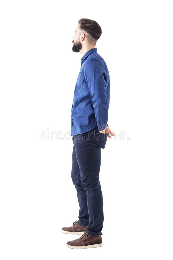 Vista laterale di giovane uomo barbuto alla moda con le mani in tasche posteriori che stanno e che guardano immagini stock