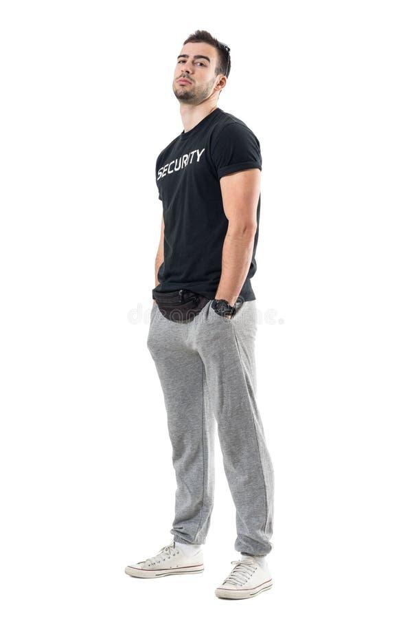 Vista laterale di giovani buttafuori macho con le mani in tasca e testa inclinate indietro fotografia stock libera da diritti