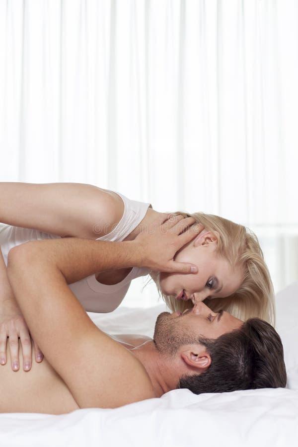 Vista laterale di giovani coppie affettuose nella camera di albergo immagini stock