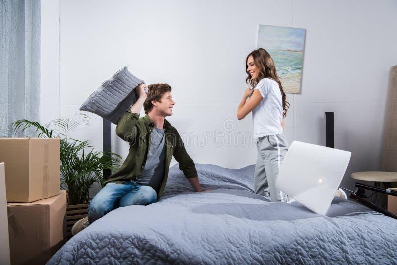 vista laterale di giovani coppie che hanno lotta di cuscino fotografia stock