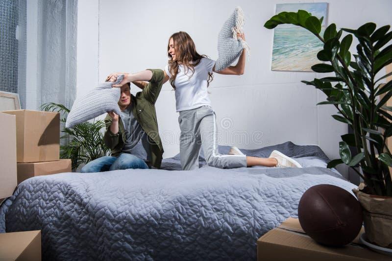 vista laterale di giovani coppie che hanno lotta di cuscino fotografie stock libere da diritti