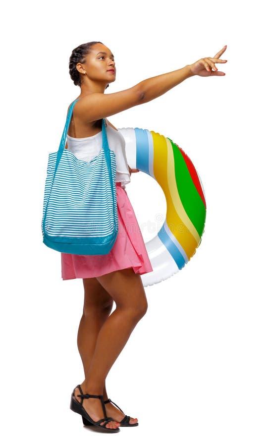 Vista laterale di indicare afroamericano con una borsa della spiaggia che va al lato immagine stock