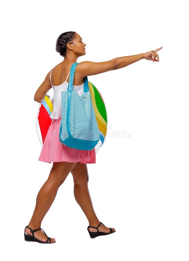 Vista laterale di indicare afroamericano con una borsa della spiaggia che va al lato fotografie stock libere da diritti