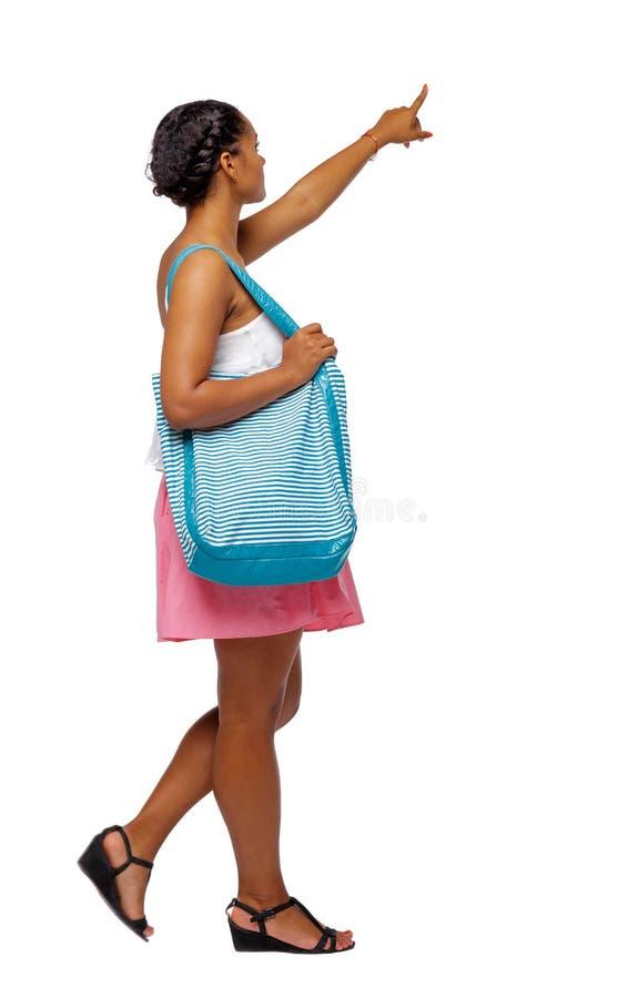 Vista laterale di indicare afroamericano con una borsa della spiaggia che va al lato fotografia stock