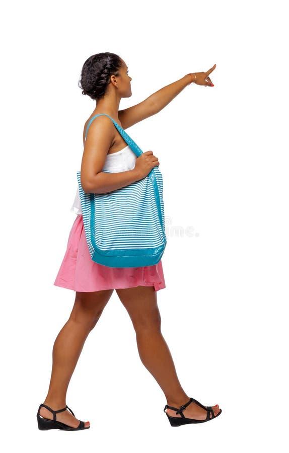 Vista laterale di indicare afroamericano con una borsa della spiaggia che va al lato fotografia stock libera da diritti